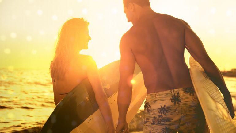 mann und frau mit surfbrett im sonnenuntergang