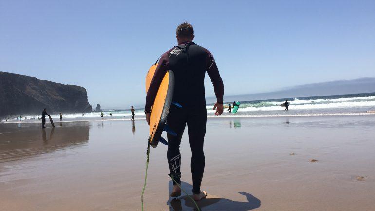 surfen mit neoprenanzug am arrifana beach portugal